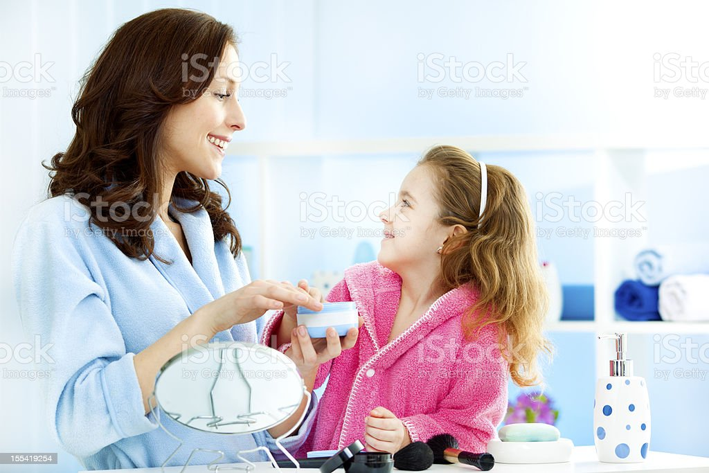 Mother and daughter putting on hand cream moisturizer royalty-free stock photo