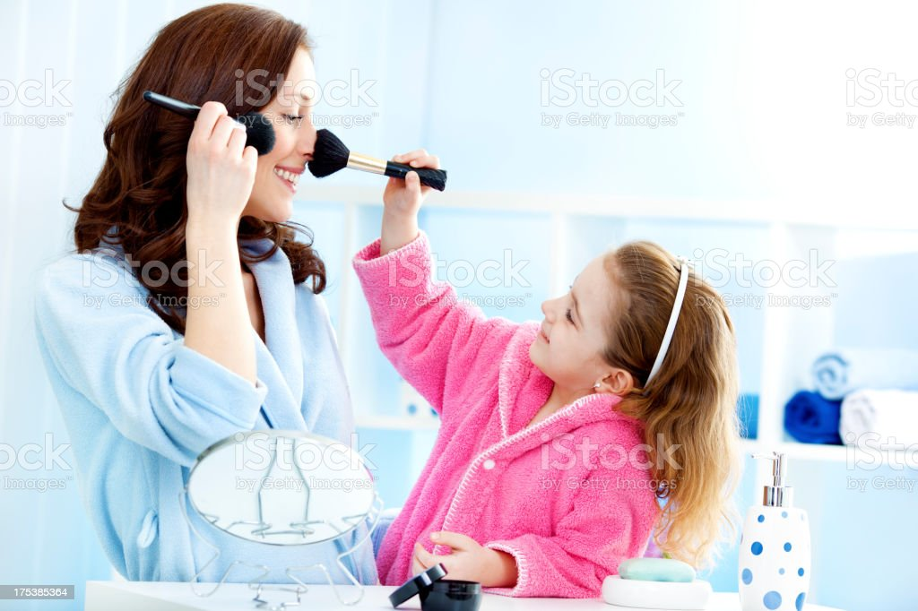 Mother and daughter putting on make up. royalty-free stock photo
