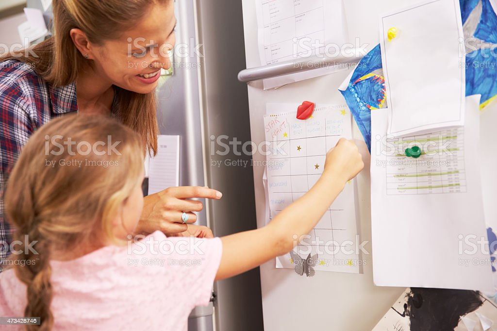 Mother And Daughter Putting Star On Reward Chart stock photo