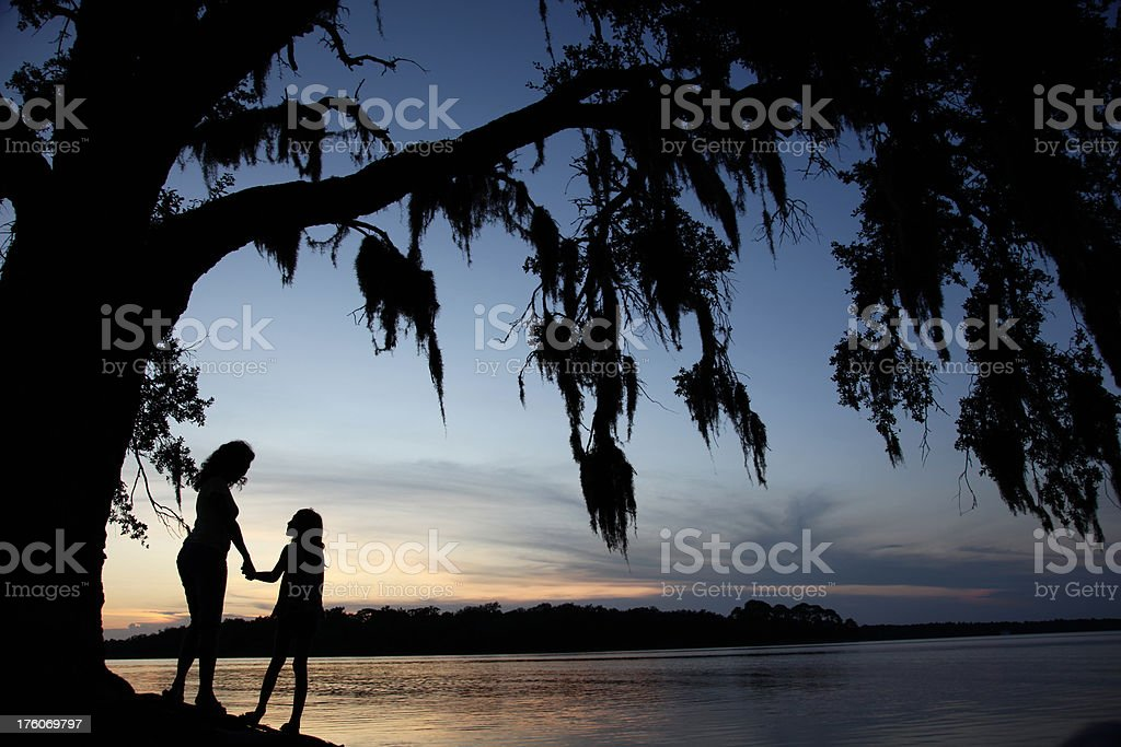 Mother and Daughter Quality Time under Tree at Sunset Silhouette royalty-free stock photo