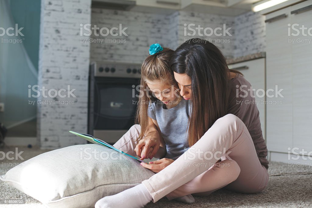 Mother and daughter reading book in the livingroom stock photo
