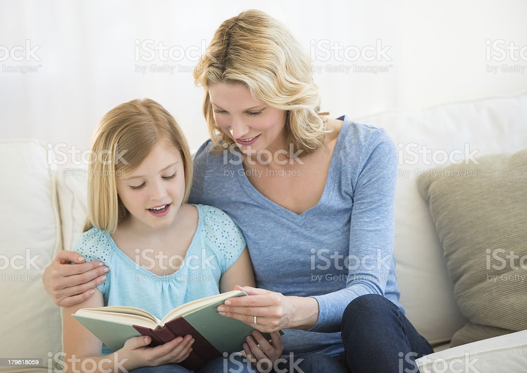 Mother And Daughter Reading Book Together On Sofa royalty-free stock photo