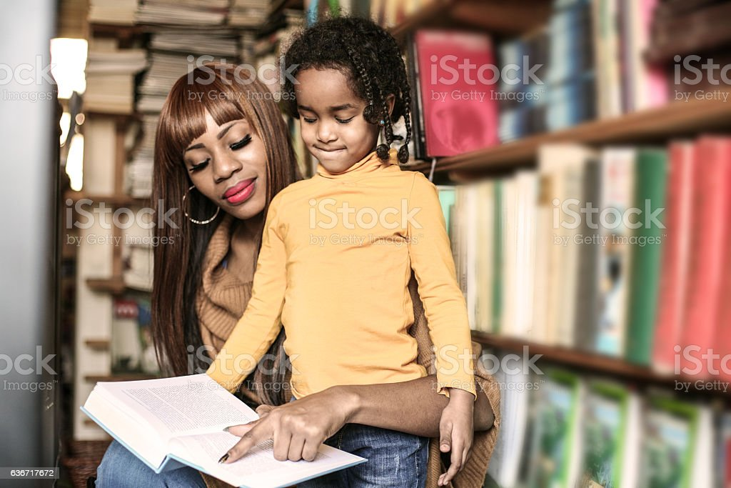 Mother and daughter reading together in library. stock photo