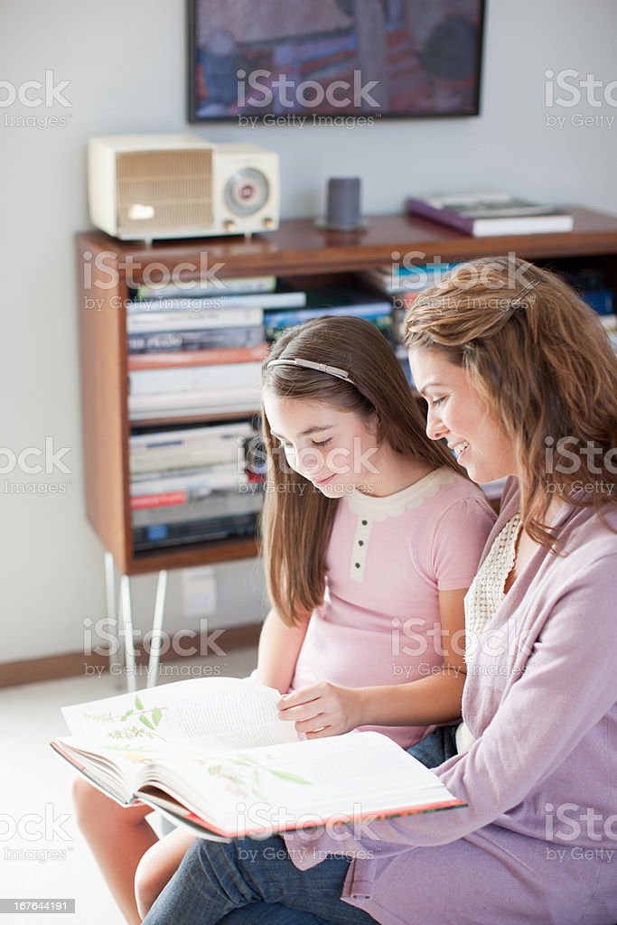 Mother and daughter reading together indoors royalty-free stock photo
