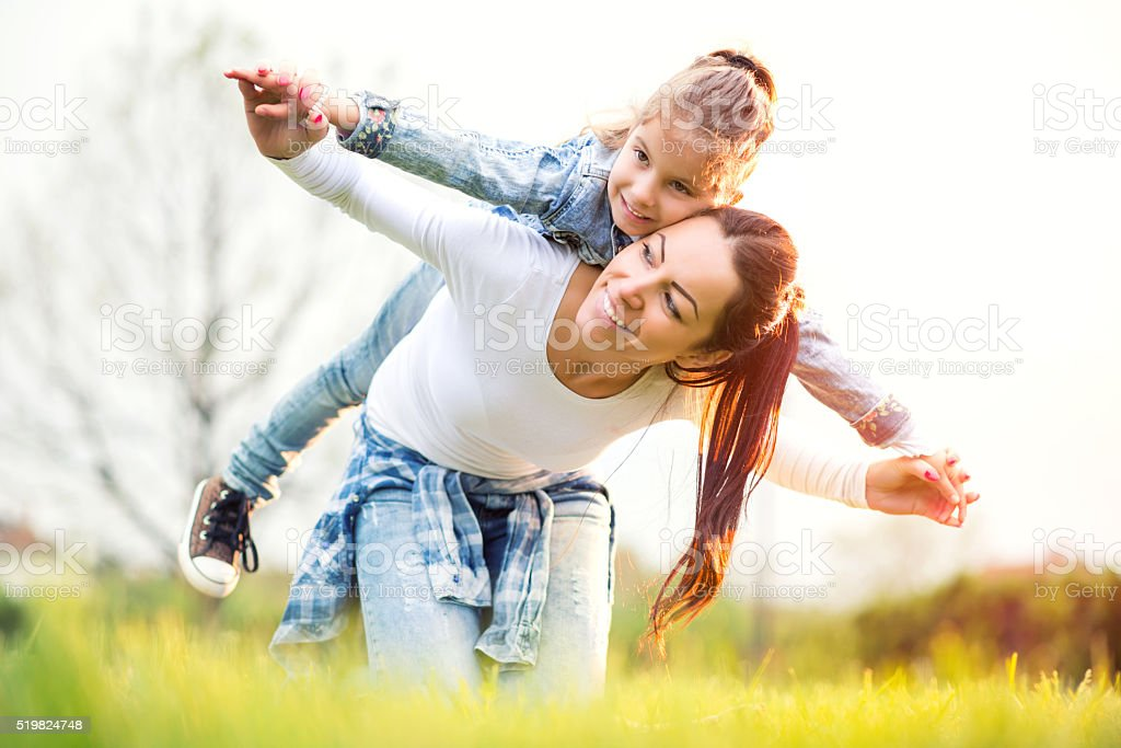 Mother and daughter relaxing together outdoor. stock photo