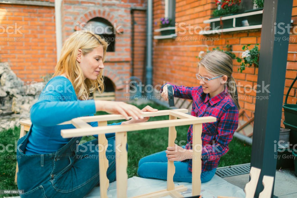 Mother And Daughter repairing furniture stock photo
