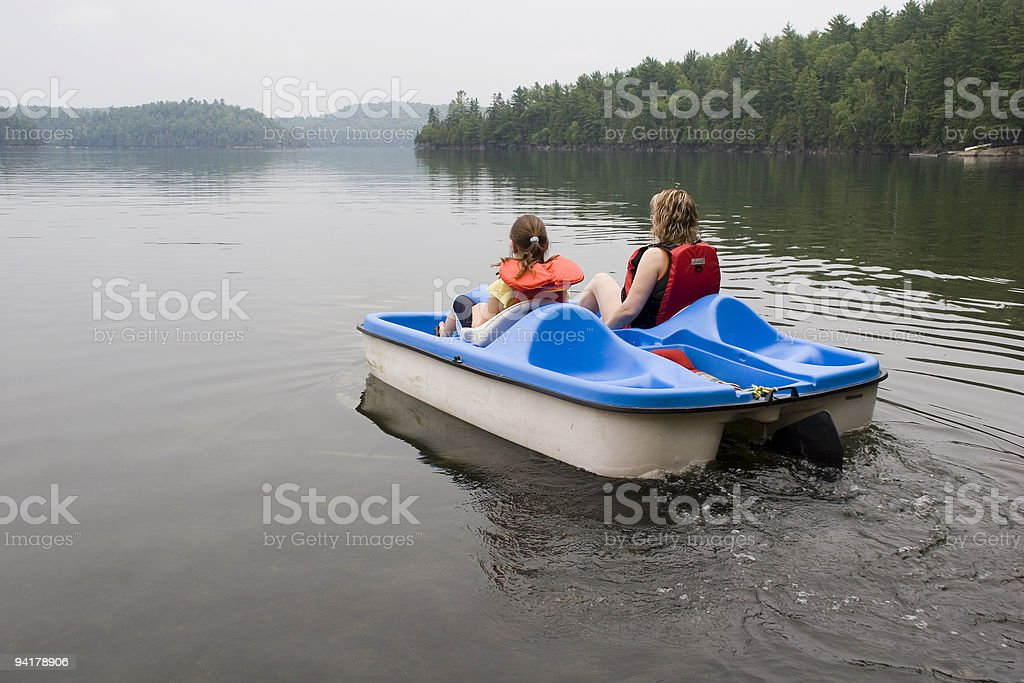 A mother and daughter riding a pedelo wearing life jackets stock photo