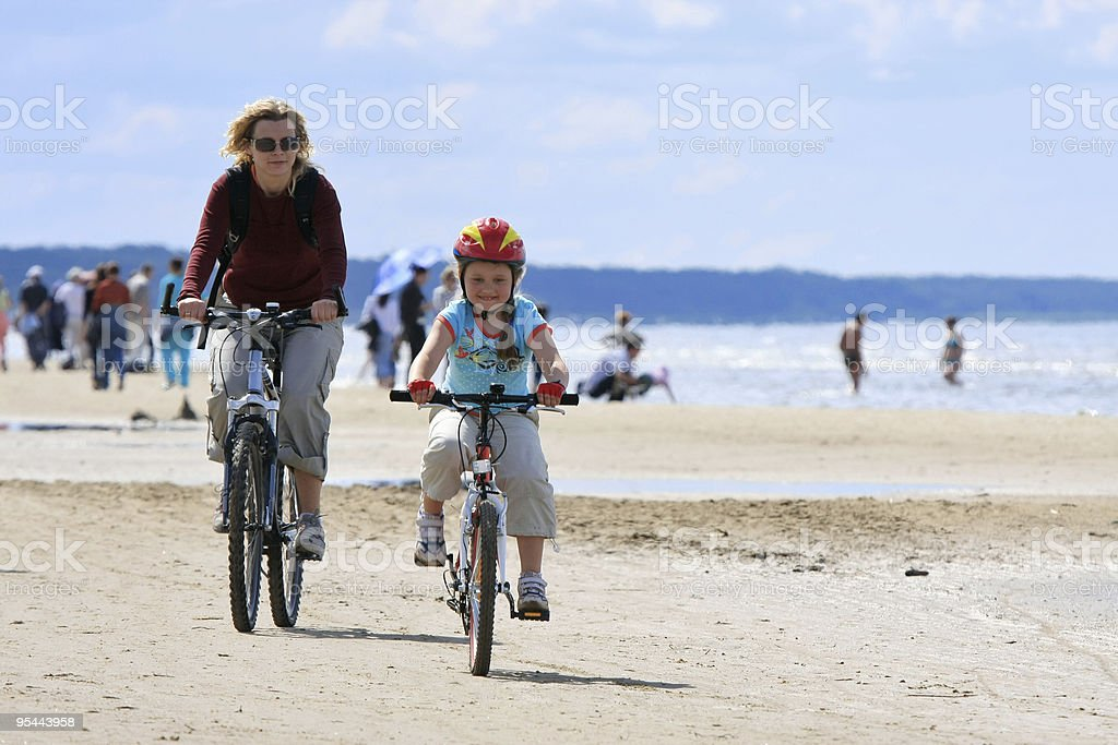 Mother and daughter riding along the beach royalty-free stock photo
