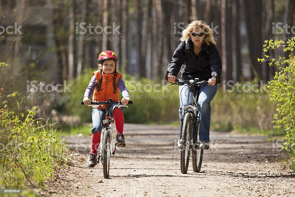 Mother and daughter riding on bicycles royalty-free stock photo