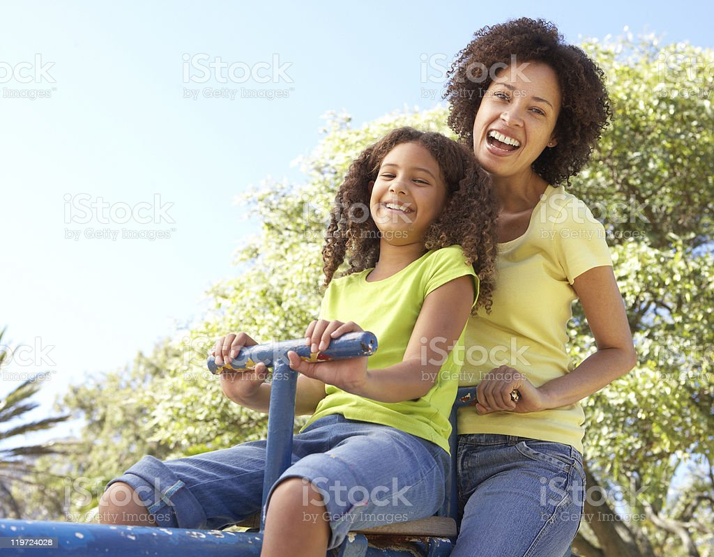 Mother And Daughter Riding On Seesaw In Park royalty-free stock photo