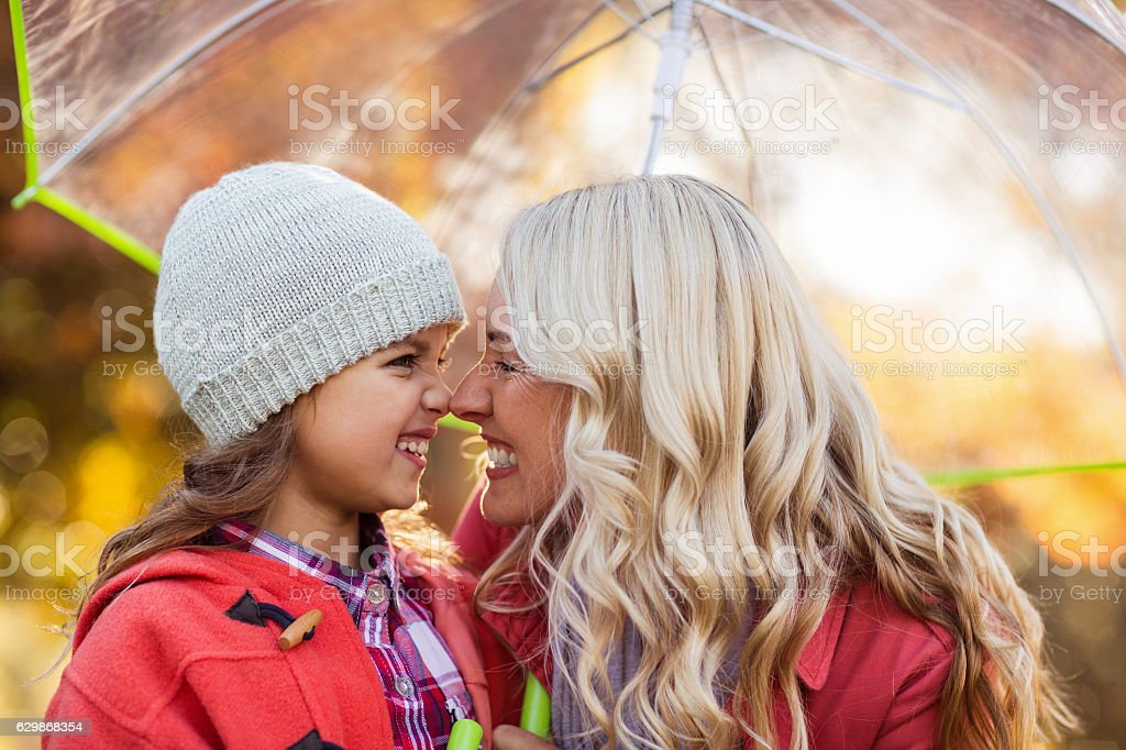 Mother and daughter rubbing noses at park stock photo