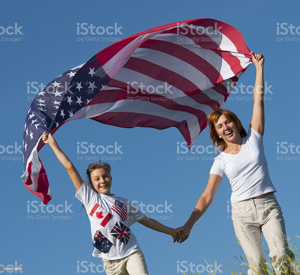 Mother and daughter run on meadow stock photo