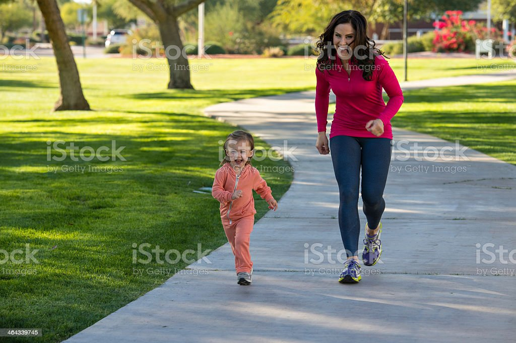 Mother and daughter running in a park stock photo