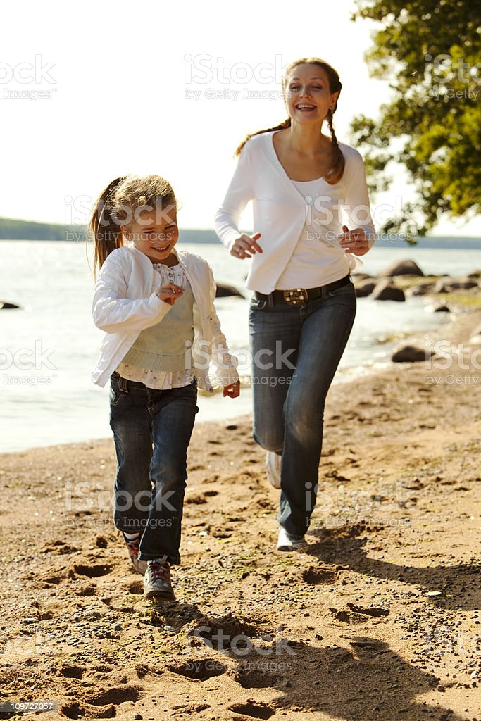 Mother and daughter running on beach royalty-free stock photo