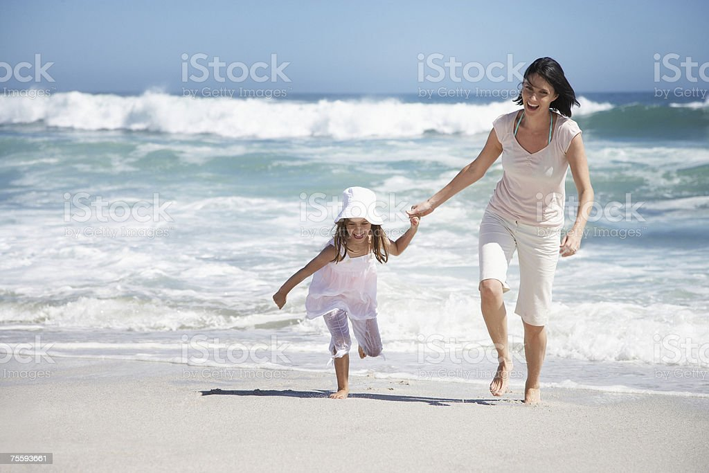 A mother and daughter running on the beach royalty-free stock photo