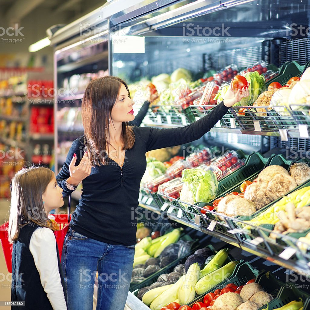Mother and daughter selecting vegetables in a supermarket royalty-free stock photo