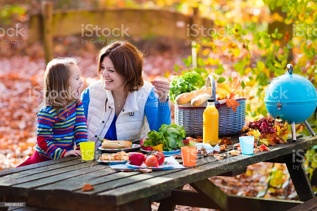 Mother and daughter set table for picnic in autumn stock photo