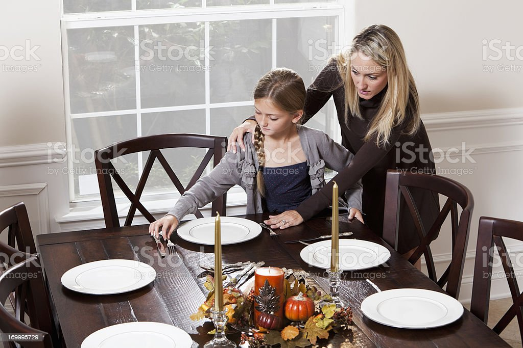 Mother and daughter setting table for dinner stock photo