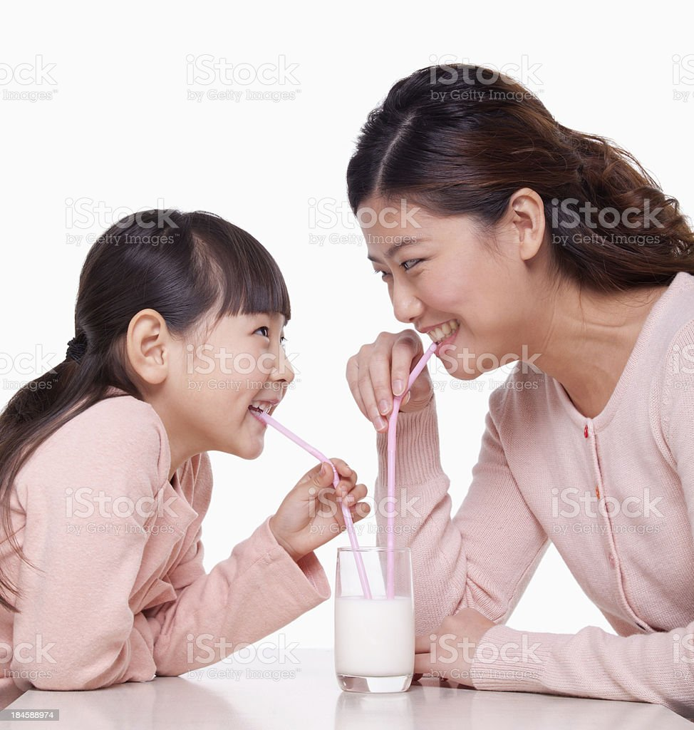 Mother and daughter sharing a glass of milk, studio shot royalty-free stock photo