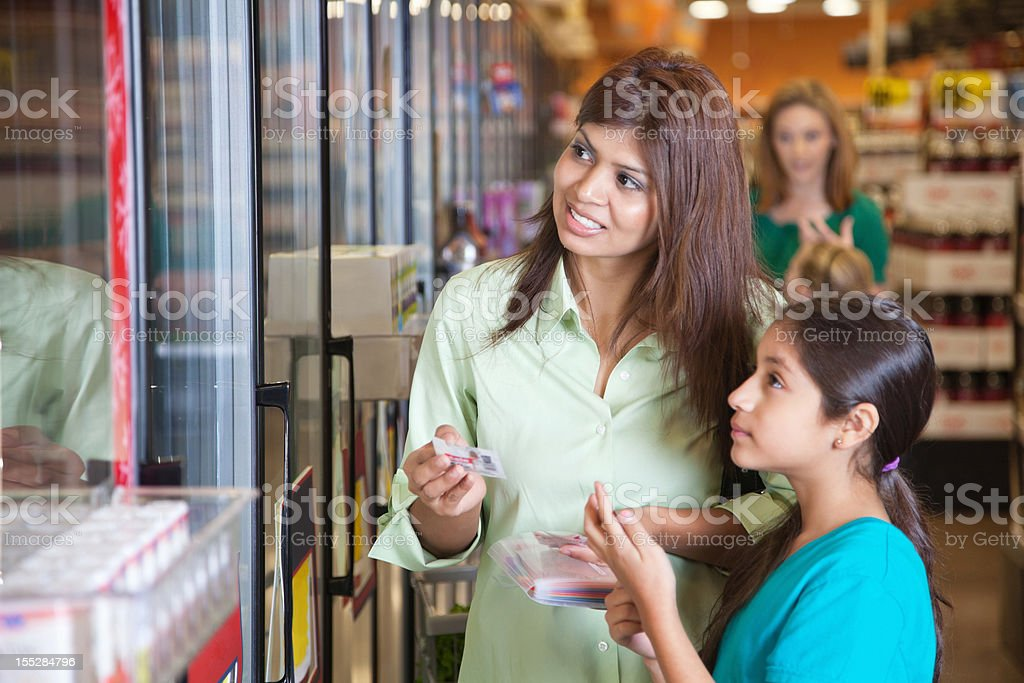 Mother and daughter shopping with coupons at the grocery store stock photo