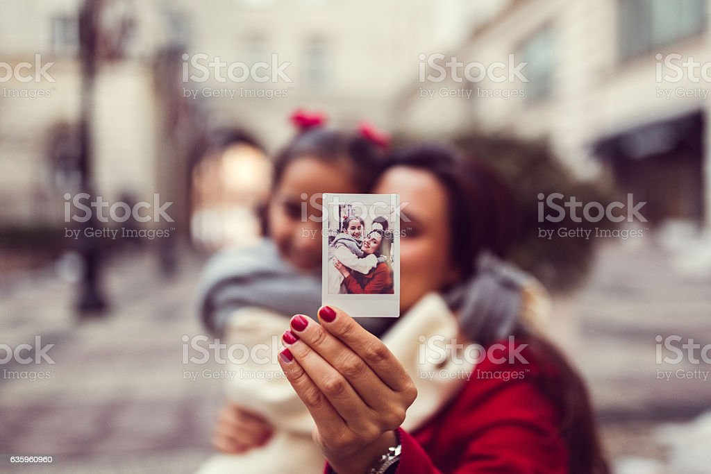 Mother and daughter showing instant photo stock photo
