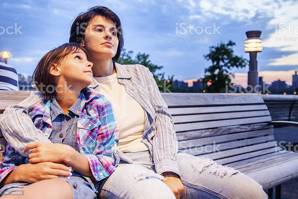 Mother and daughter sits at the bench royalty-free stock photo