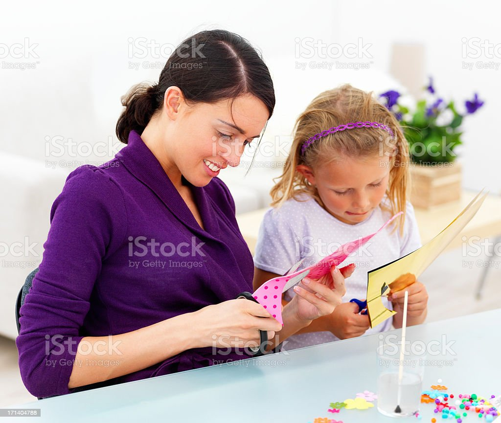 Mother and daughter sitting at desk and cutting color papers royalty-free stock photo