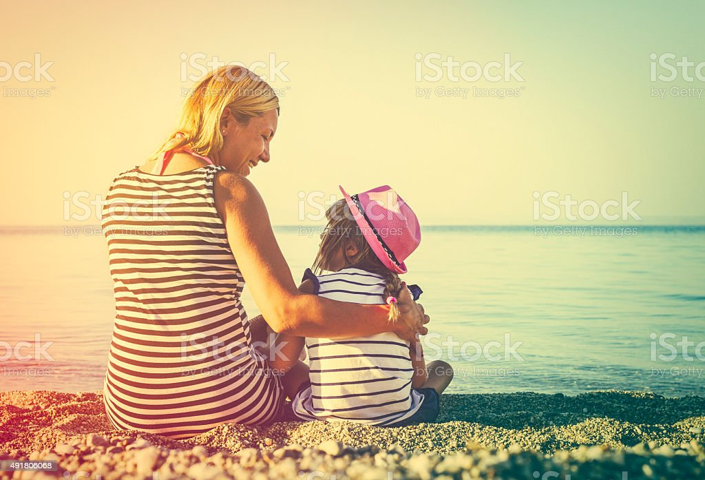 Mother and daughter sitting at the beach together at sunset stock photo