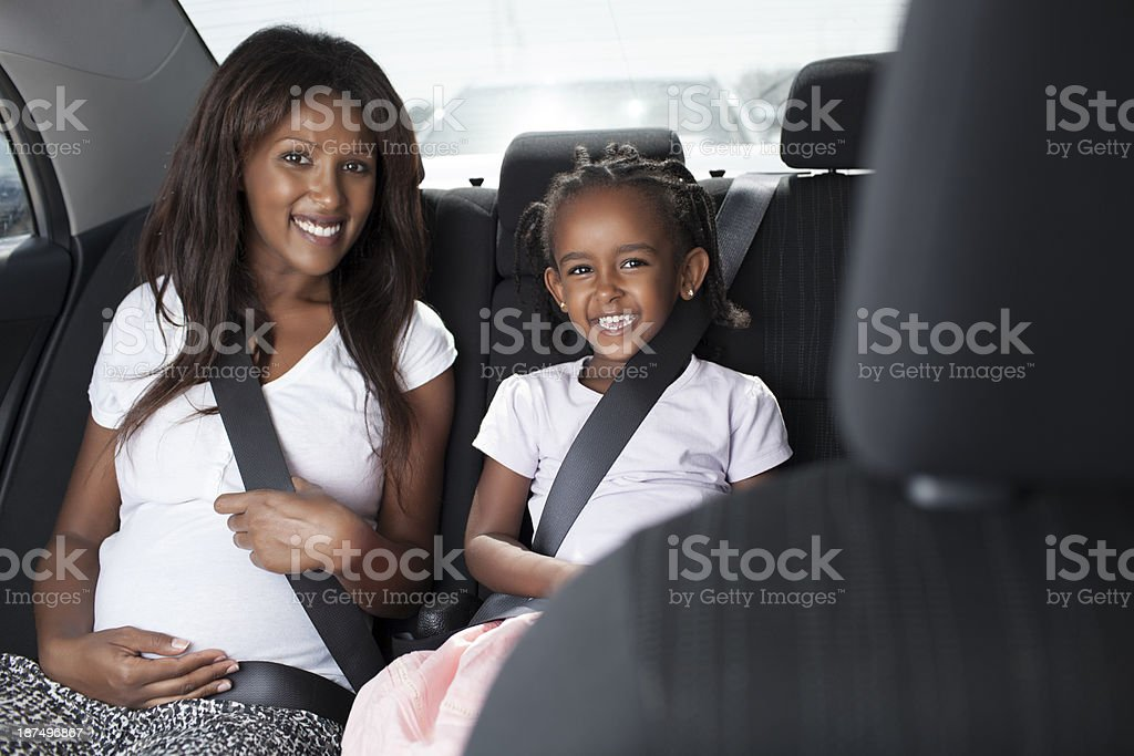 Mother and daughter sitting in backseat of the car. royalty-free stock photo
