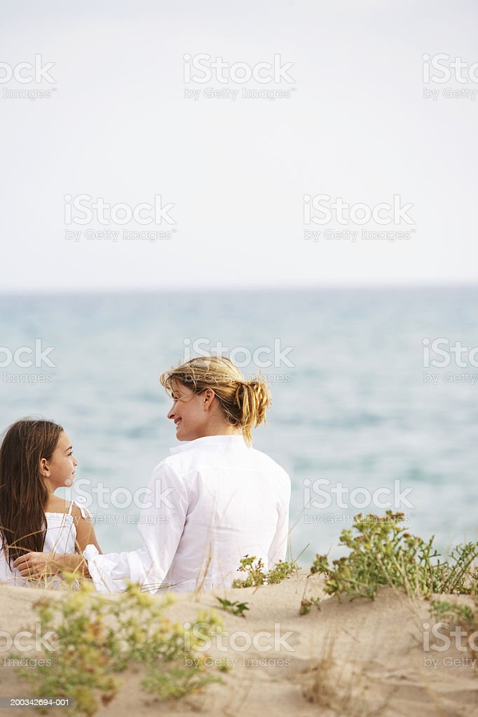 Mother and daughter (6-8) sitting in sand dunes, rear view stock photo