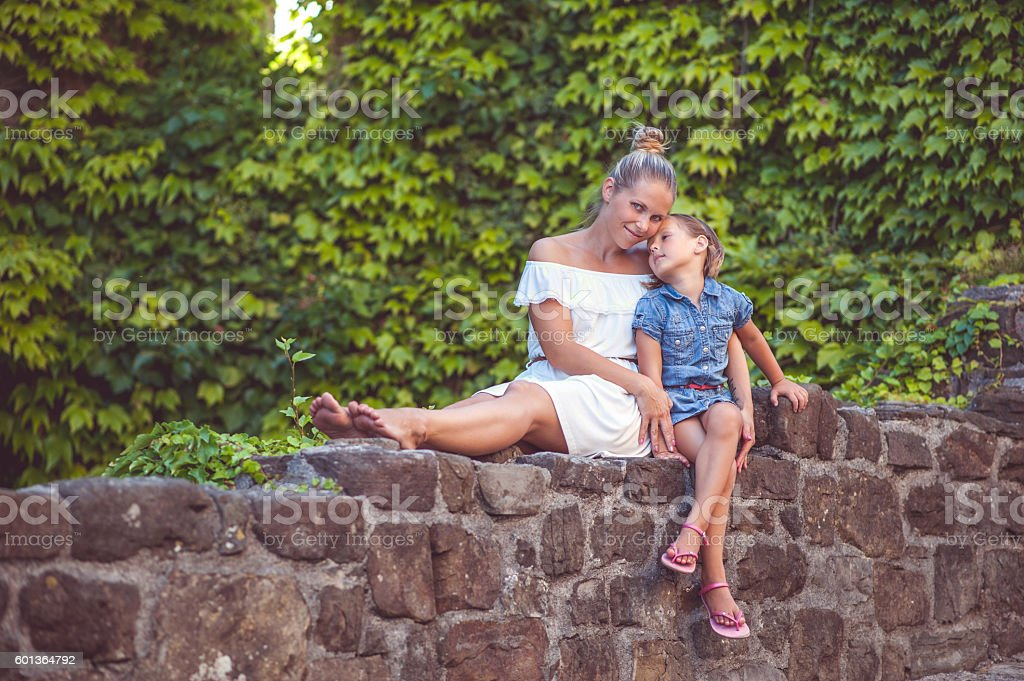 Mother And Daughter Sitting On A Stone Wall stock photo