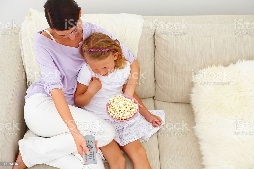 Mother and daughter sitting on couch eating popcorn royalty-free stock photo