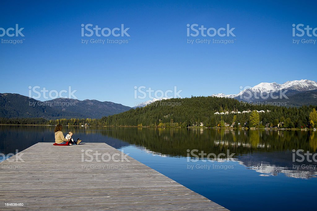 mother and daughter sitting on dock royalty-free stock photo