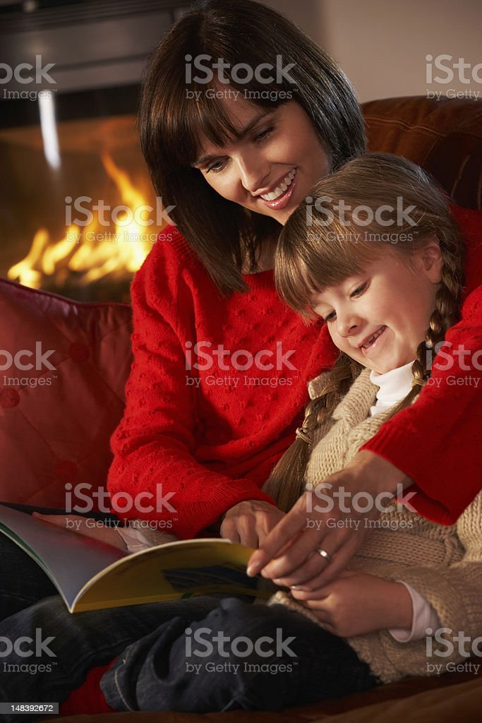 Mother And Daughter Sitting On Sofa Reading Book By Fire royalty-free stock photo