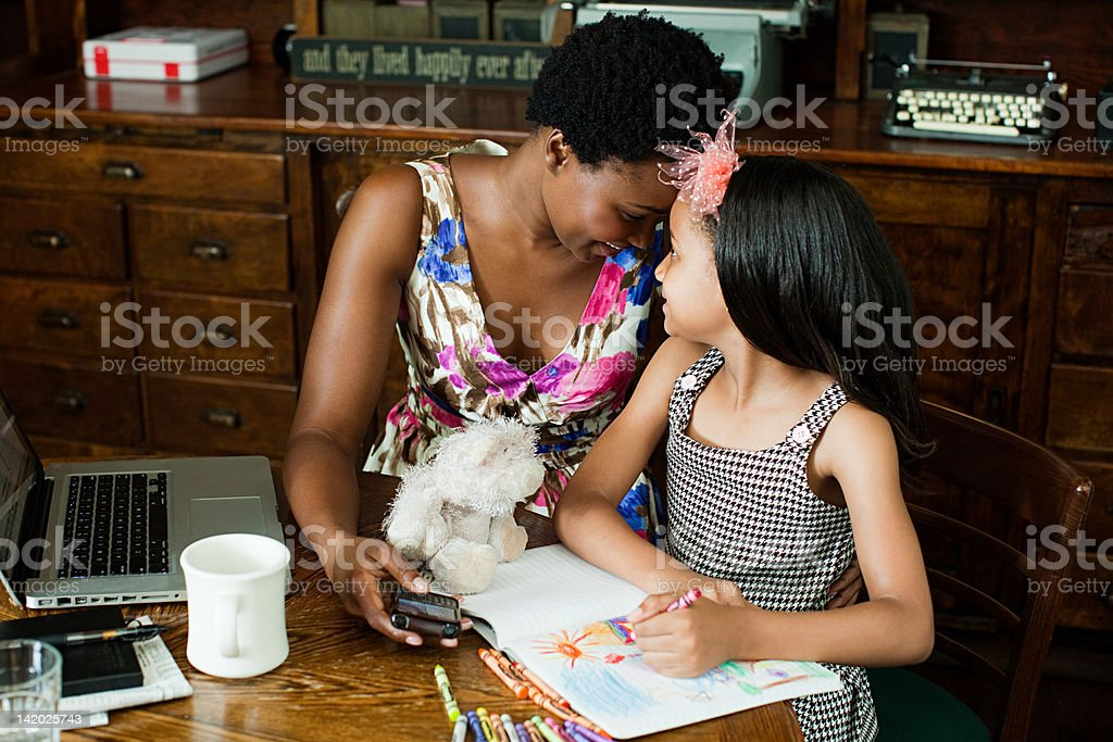 Mother and daughter sitting together at home stock photo
