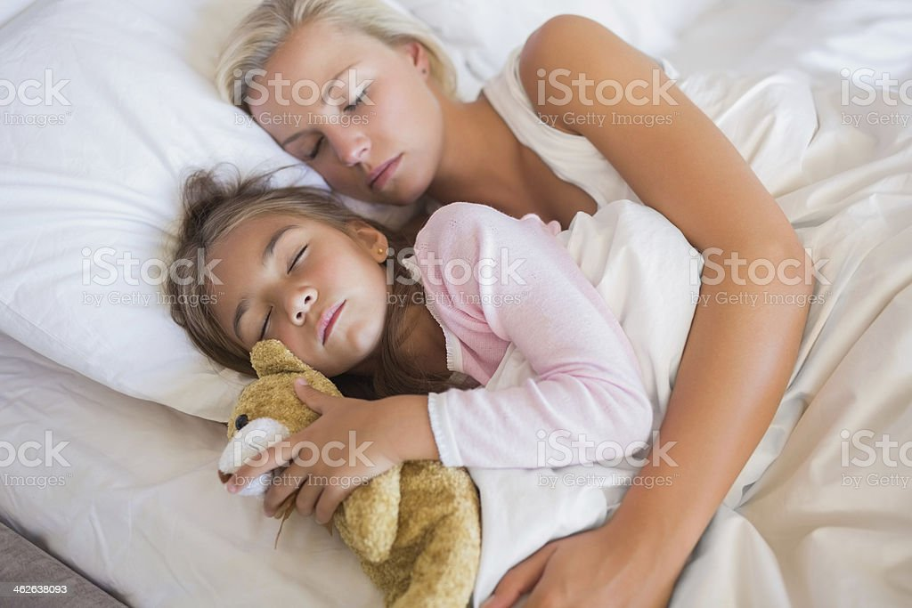 Mother and daughter sleeping in bed royalty-free stock photo