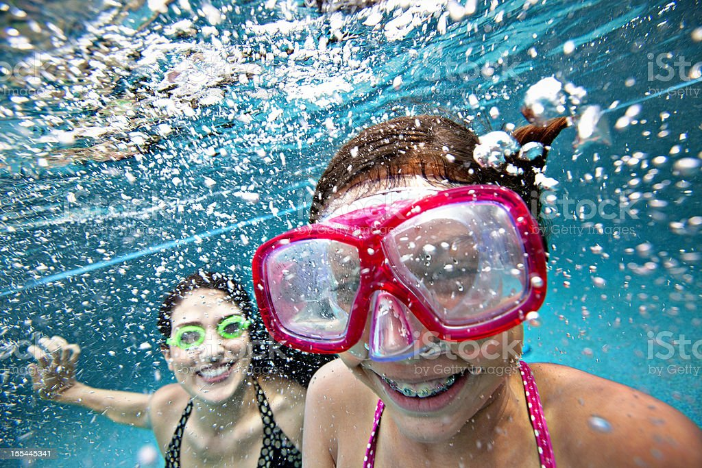 Mother and daughter smiling underwater in pool stock photo