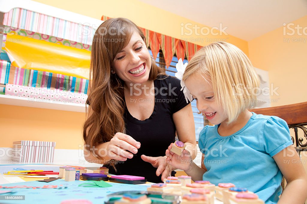 Mother and daughter smiling while making arts and crafts stock photo
