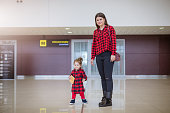 Mother and daughter standing in airport hall