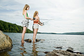 Mother and daughter standing in lake fishing together