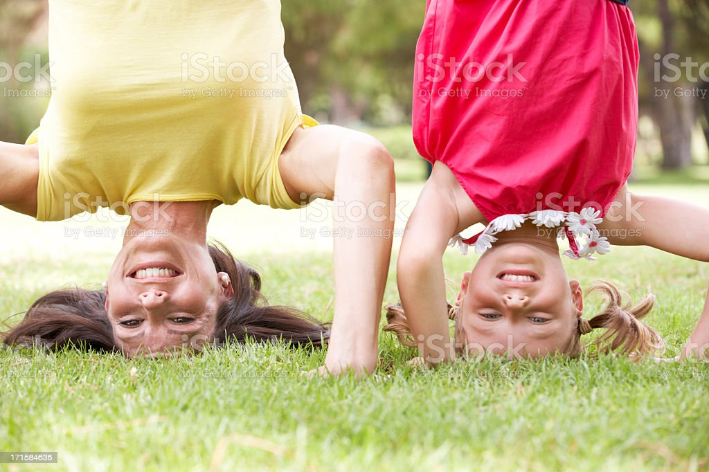 Mother And Daughter Standing On Their Heads In Garden stock photo