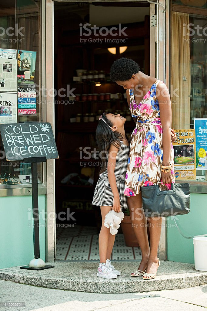 Mother and daughter standing outside coffee shop stock photo