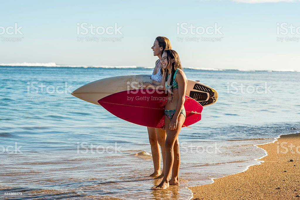 Mother and daughter surfers stock photo