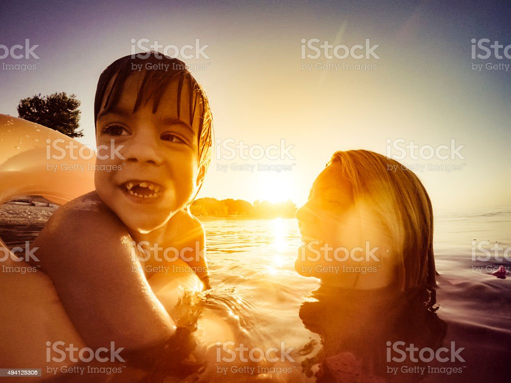 Mother and daughter swimming at sunset stock photo