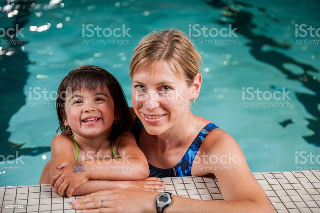 Mother and Daughter Swimming in the Pool stock photo