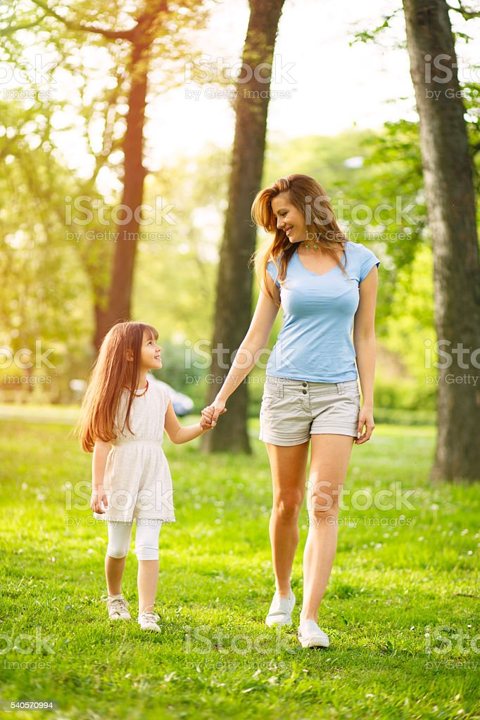 Mother and daughter taking a walk in the park. stock photo