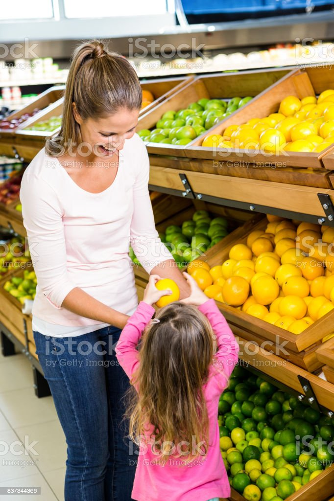 Mother and daughter taking fruit stock photo