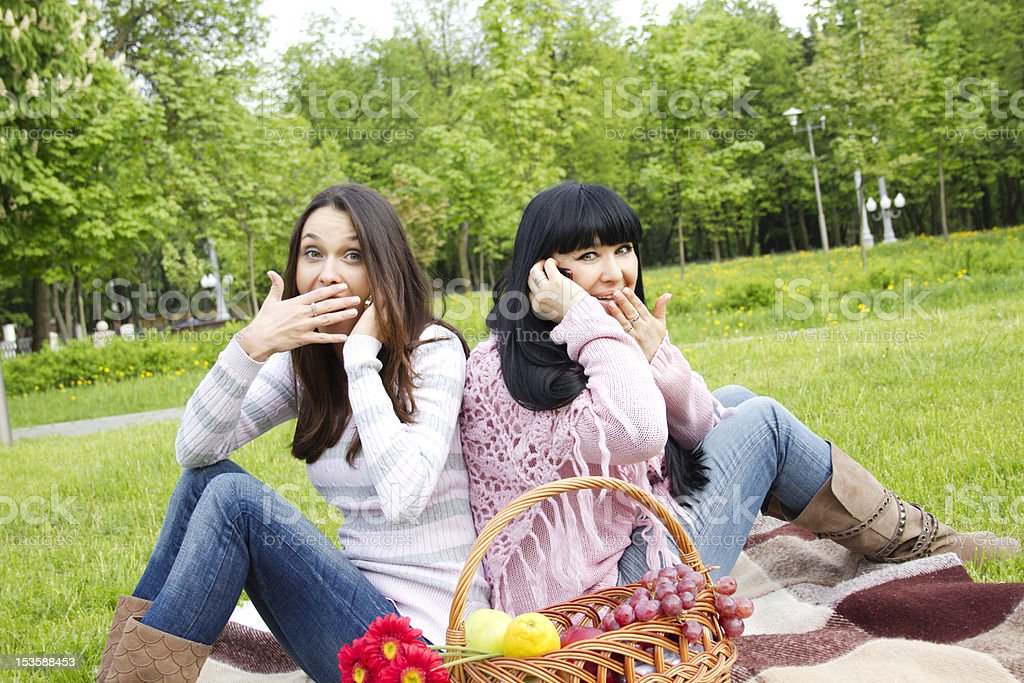 Mother and daughter talk on the phone in park royalty-free stock photo