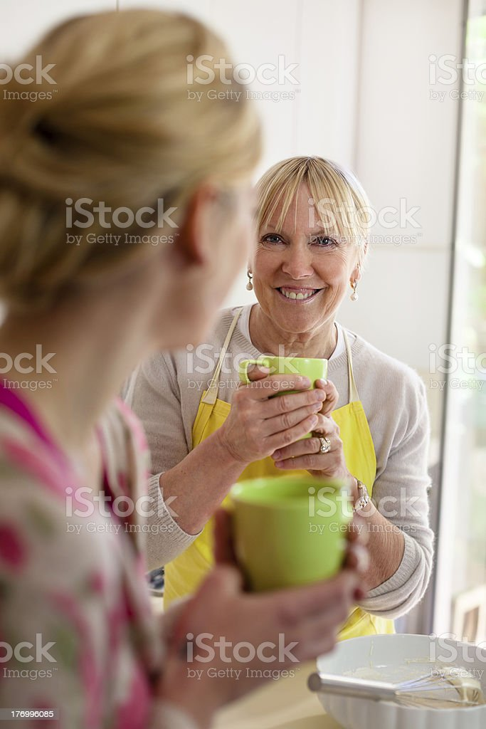 Mother and daughter talking, drinking coffee in kitchen royalty-free stock photo