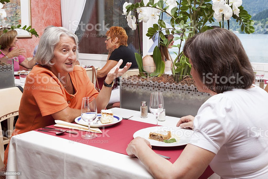 Mother and daughter talking in a restaurant stock photo